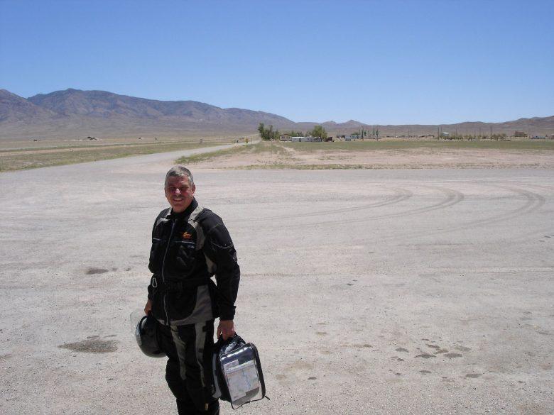 Bild eines Motorradfahrers mit Helm und Tankrucksack bei einer Rast an der Area 51 in Rachel, NV (USA) bei 45° C, weil er versaeumt hat, beste Picknickplaetze fuer Motorradfahrer zu finden