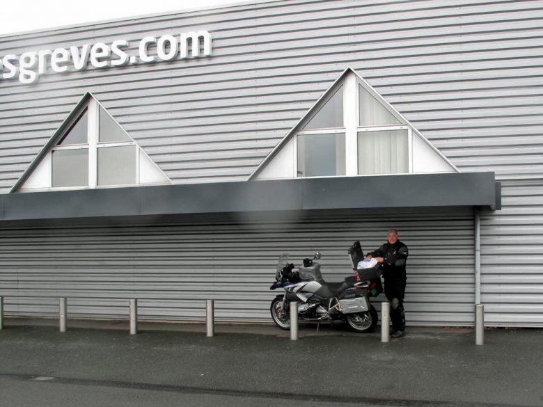 Motorradfahrer in schwarzer Kombi mit einer BMW R 1200 GS unter dem Vordach eines Hypermarché in Frankreich bei Regen