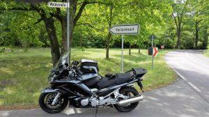 Bild einer schwarzen Yamaha FJR am Rande der Landstraße vor einem Verkehrsschild mit der Aufschrift Verlorenort