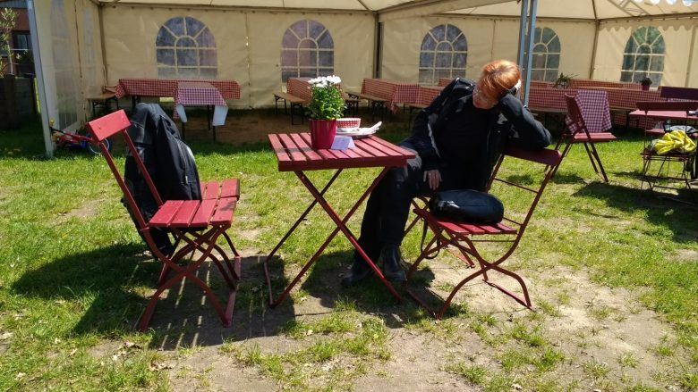Bild einer rothaarigen Motorradfahrerin in einem Gartenlokal beim langen Warten auf das Essen