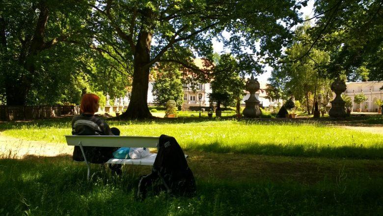 Bild einer Motorradfahrerin beim Picknick auf einer Bank im Schloßpark von Wiepersdorf in Brandenburg