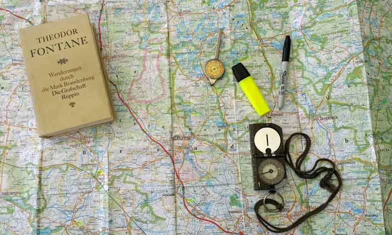 Landkarte mit Kompass, Stifzen und einem Band von Theodor Fontanes Wanderungen durch die Mark Brandenburg