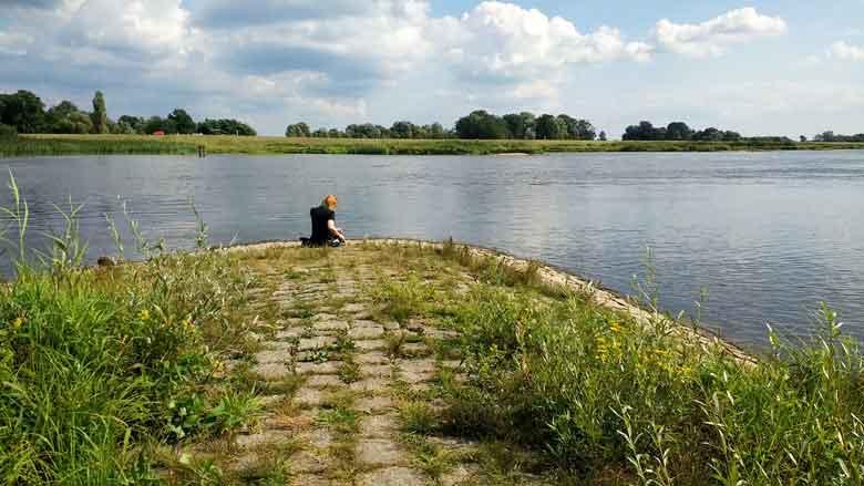 Bild einer rothaarigen Motorradfahrerin am Oderstrand bei Lebus während eines Picknicks am Fluss bei einer Motorradtour Spree Oderland