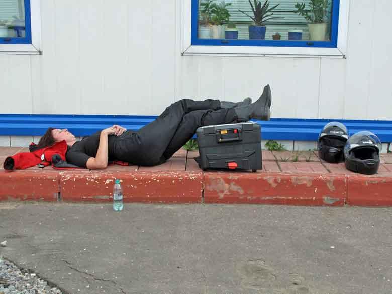 Rothaarige Motorradfahrerin liegend bei einer Ruhepause an einer Tankstelle mitten in Russland