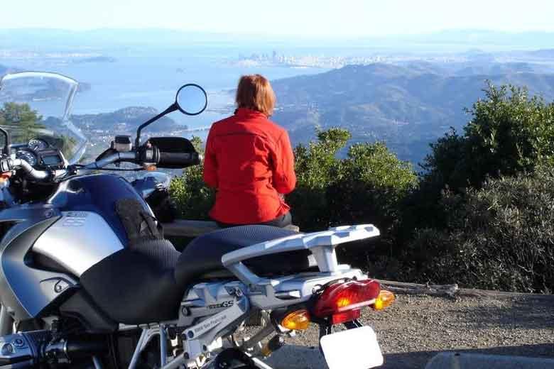 Rothaarige Motorradfahrerin in roter Kombi vor einer BMW R 1200 GS mit Blick vom Mt. Tamalpais auf die San Francisco Bay in Kalifornien
