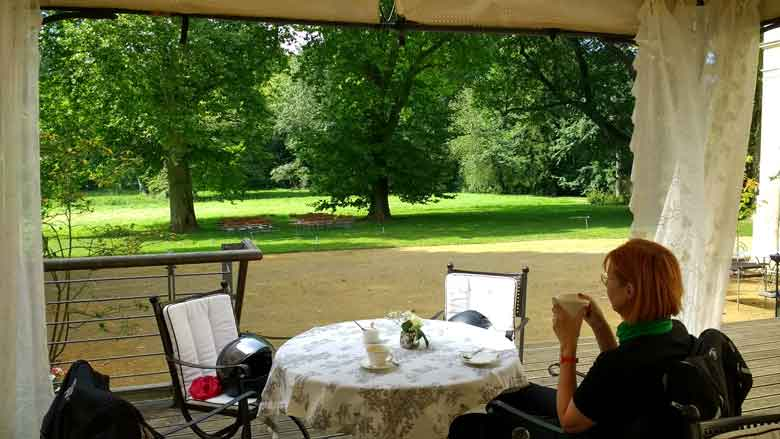 Bild einer rothaarigen Motorradfahrerin auf der Terrasse des klassizistischen Schlosses Steinhoefel beim Kaffee trinken waehrend einer Motorradtour Spree Oderland
