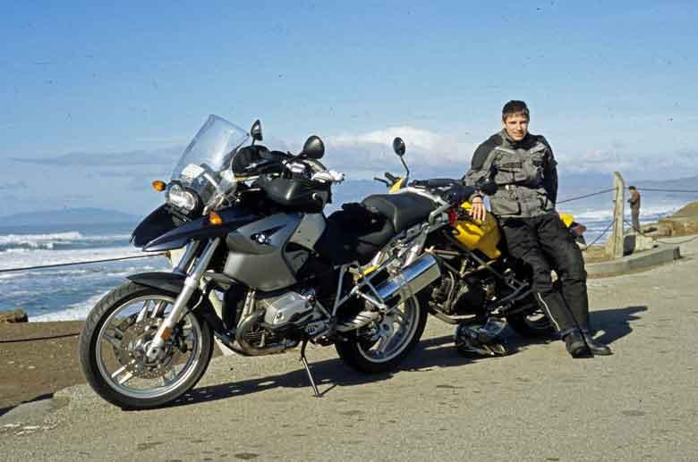Bild eines jungen Mannes mit seinem gelben Motorrad Ducati Monster 750 bei einem Technischer Halt auf der CA 1 bei der Skyline Boulevard Motorradtour in Kalifornien