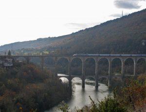Bild der Eisenbahnbruecke bei Bolzon in den Gorges de l'Ain mit TGV bei der Ueberfahrt