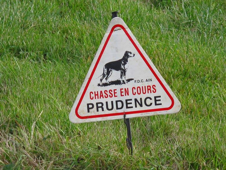 Warnschildes mit Jagdhund bei einer Treibjagd und der Aufschrift Chasse en cours Prudence