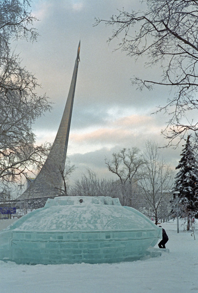 Bild vom Raketendenkmal am Kosmonautenmuseum in Moskau im Winter mit einer aus Eis gebauten Raumkapsel im Vordergrund