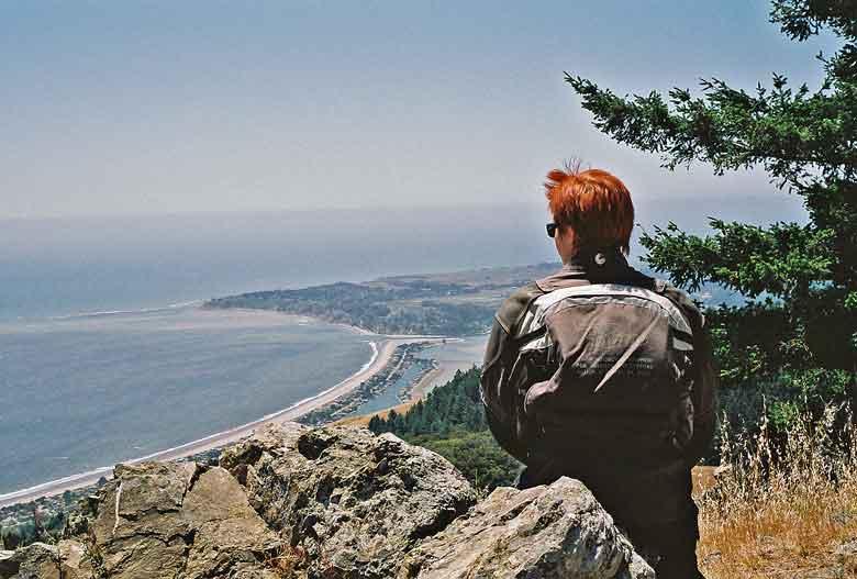Rothaarige Motorradfahrerin vom Berg aus auf das Meer bei Stinson Beach in Kalifornien blickend