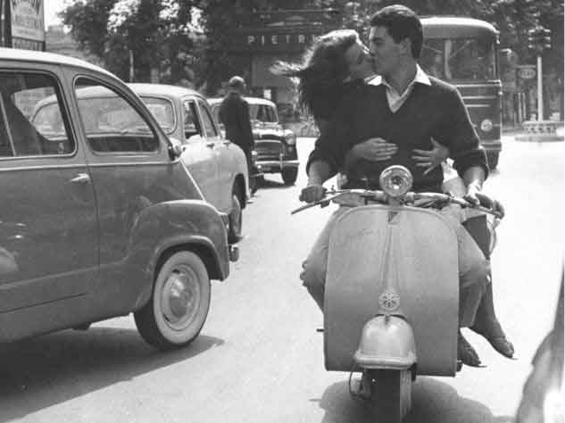Junges Paar auf einer Vespa im Stadtverkehr als Beispiel für Harmonie mit der Sozia im Sattel