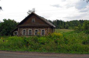 Bild Russisches Holzhaus mit sparrenförmigen Verzierungen am Strassenrand und verwildertem Garten