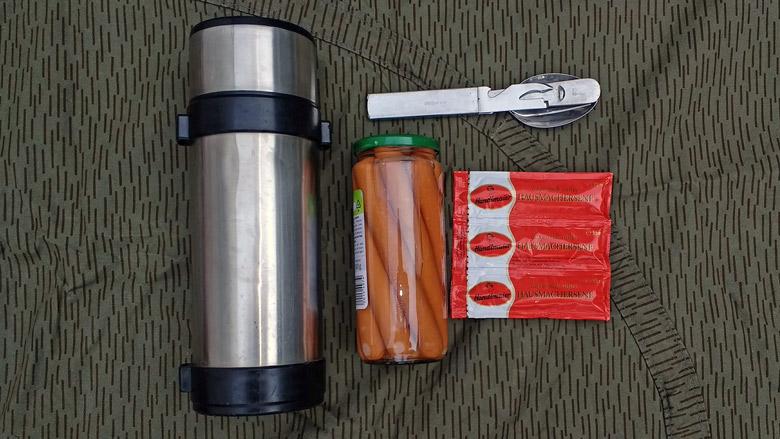 Bild einer Thermosflasche, eines Glases Wiener Wuerstchen, einer Dreierpackung Senf und eines Feldessbestecks als deftige Methode fuer Essen auf Raedern im Winter
