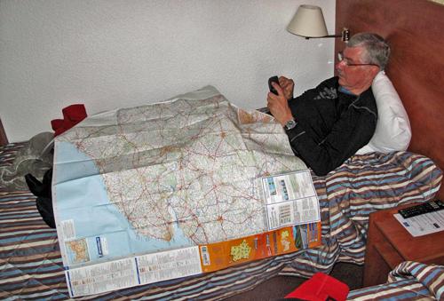 Beste Smartphone-Apps fuer Motorradtouren beginnen mit einfachen Dingen: Bild von einem Mann im Bett mit einer Landkarte auf den Knien und einem Navi in den Händen, in das er die Streckendaten eingibt