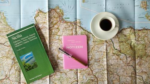 Bild eines Notizbuches, eines italienischen Reisefuehrers und einer Tasse Espresso auf einer Landkarte von Sizilien