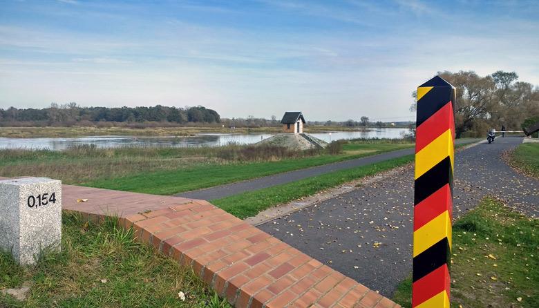 Bild von der Oder-Neisse-Grenze mit einem schwarz-rot-goldenen Grenzpfahl im Vordergrund und einem Pegelhäuschen am Ufer der Oder