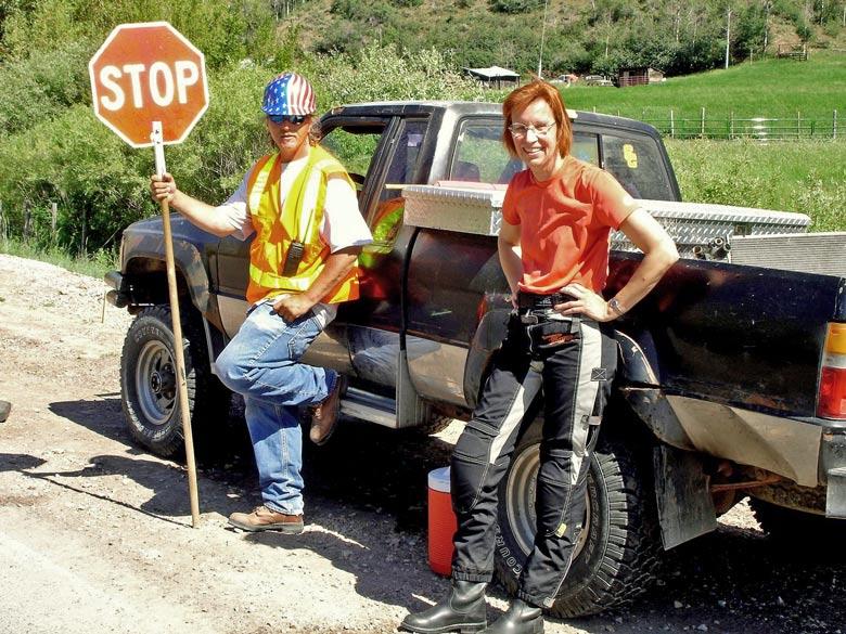 Straßenbauarbeiter mit einem Stopschild in der Hand neben einer rothaarigen Motorradfahrerin vor einem Truck