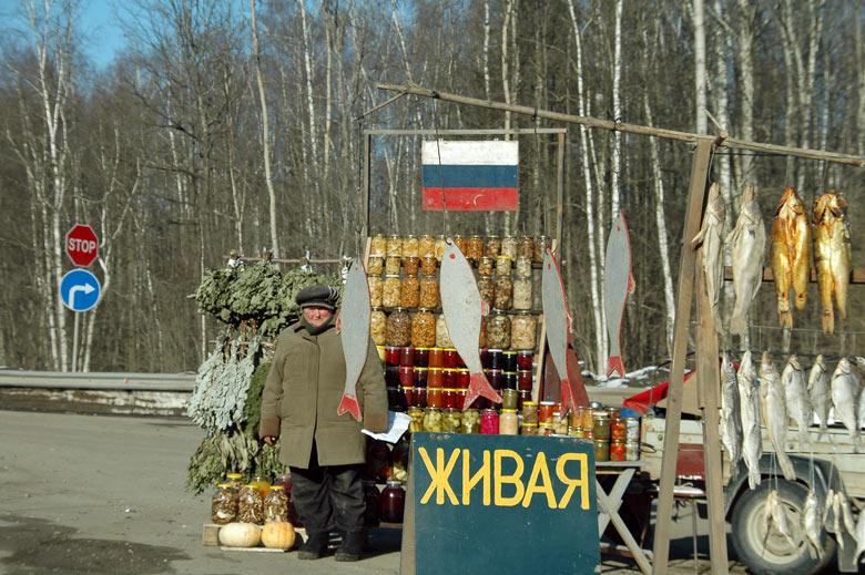 Warm angezogene Verkäuferin vor einem Fischverkaufsstand an einer russischen Landstraße im Winter mit getrockneten Fischen