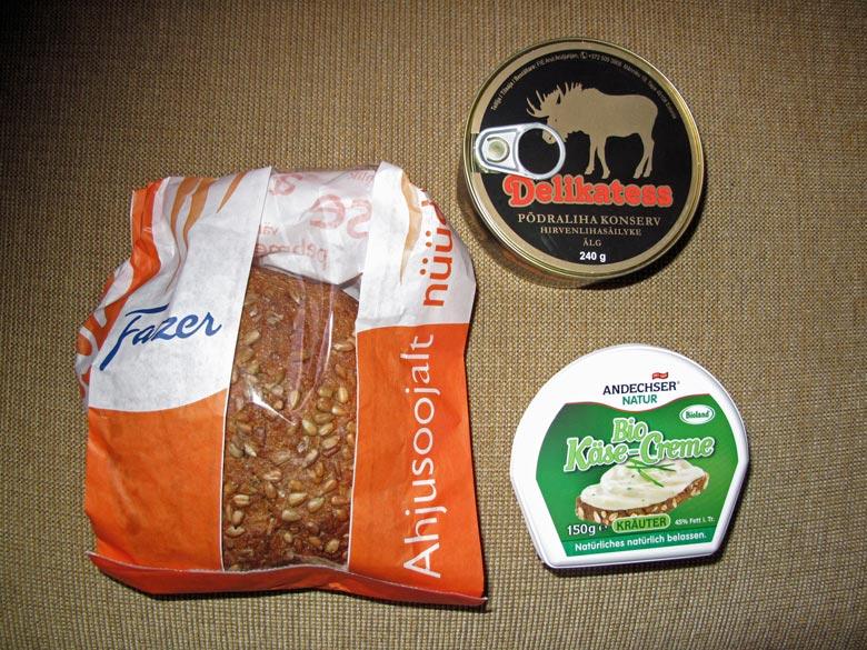 Eingepacktes Brot, eine Schachtel Käse und eine Dose Elchpastete als Picknick