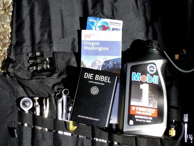 Schwarze Werkzeugrolle mit verschiedenen Werkzeugen, Landkarten, einer Dose Öl und einer Bibel