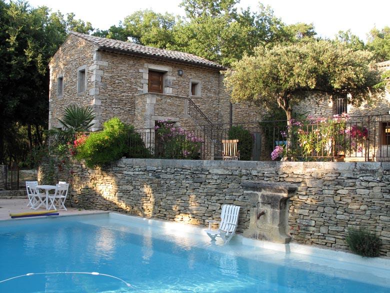 Bild von einem schön umgebauten steinernen Bauernhaus mit Swimming Pool im Vordergrund, das als Tourquartier in Faucon dient