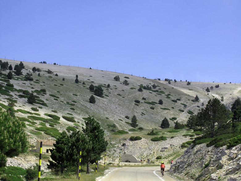 Steiniger Anstieg bei einer Motorradtour zum Gipfel des Mont Ventoux im Bild mit Felsen beiderseits der Strasse, vereinzelten Bueschen und Baeumen und schwarz-gelben Begrenzungsstangen sowie Radfahrern auf der Bergfahrt.