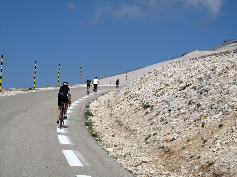 Bild von der Anfahrt zum Mont-Ventoux-Gipfel mit einigen Radfahrern auf den letzten Serpentinen einer Motorradtour zum Gipfel des Mont Ventoux an einem steinigen Hang entlang und mit Blick auf die Bergstation im Hintergrunde