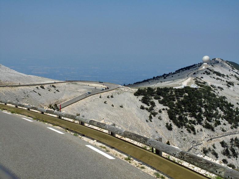 Gipfelblick vom Mont Ventoux mit Serpentinen und einem Radardom auf dem steinigen Nebengipfel