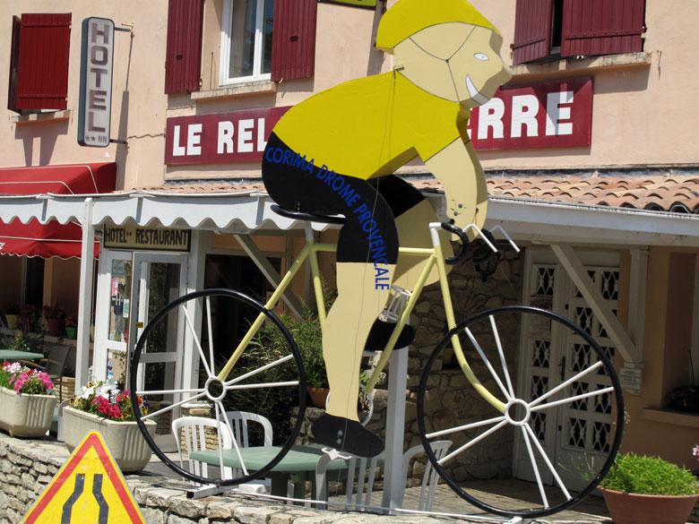 Bild von einem Pappradler an der Tour de France Strecke auf den Mont Ventoux mit einem Hotel Cafe im Hintergrund