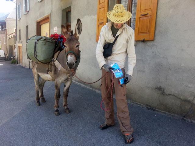 Wanderer mit einem bepackten Esel in einem französischen Gebirgsdorf bei einer Tour in die Chartreuse