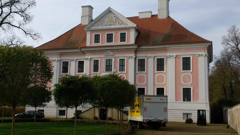 Bild der Vorderansicht Schloss Gross Rietz in der Niederlausitz mit Moebelwagen beim Einzug der neuen Mieter