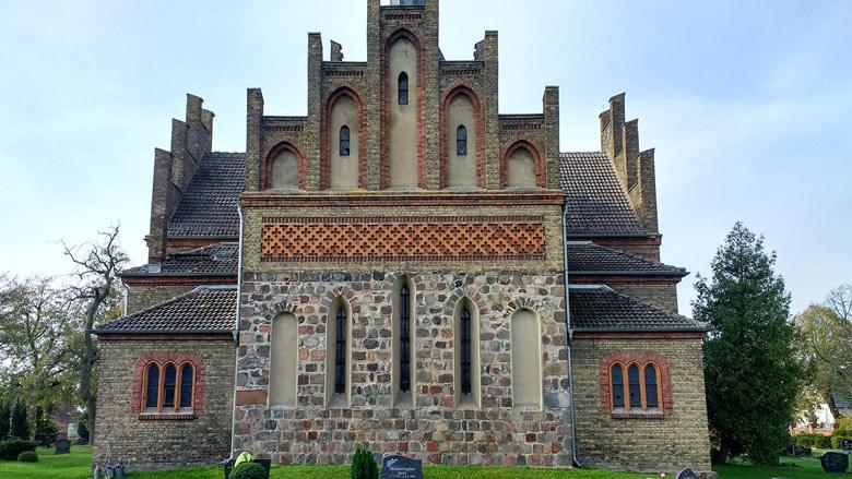 Bild der Ostansicht Kirche Herzberg mit neun Schachbrettsteinen und dem Friedhof im Vordergrund