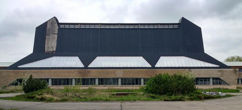 Ehemalige Hutfabrik Luckenwalde Frontansicht mit einem lang gestreckten Gebäude mit hohem schwarzen Aufbau uns einem mit Büschen bewachsenen Vorplatz im Vordergrund