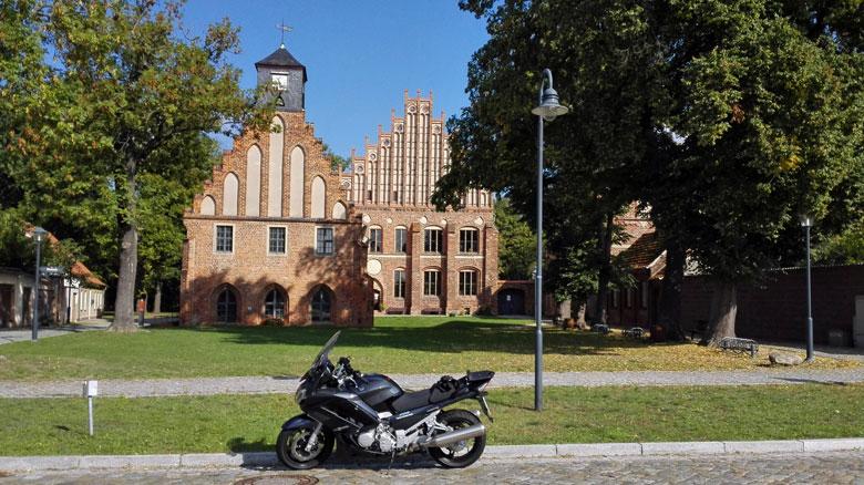Bild vom Kloster Zinna mit Museumsgebäude und Klosterbrennerei und einem Motorrad im Vordergrund