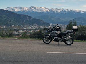 Auffahrt zum winterlichen Vercors mit einer BMW R 1200 GS im Vordergrund und der Schneebedeckten Alpenkette im Hintergrund, dazwischen der Talkessel mit der Stadt Grenoble in Frankreich