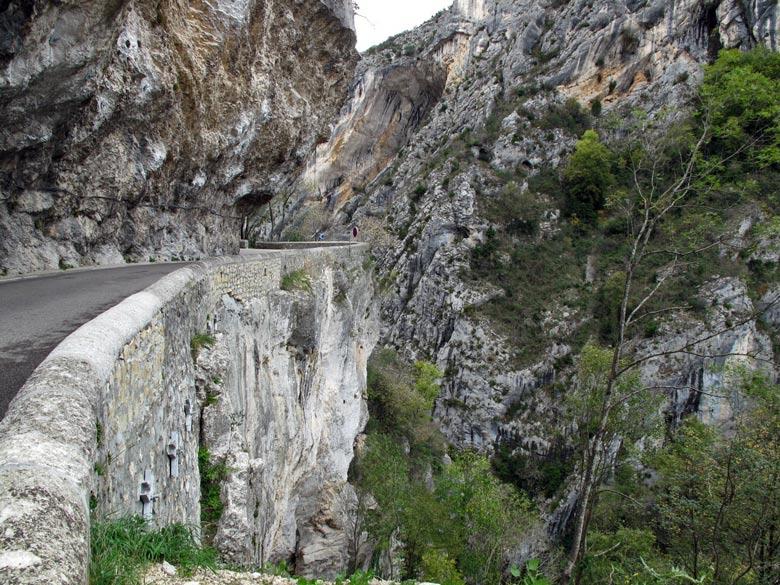 Bild von einer Felsenstrasse im winterlichen Vercors mit steil abstürzenden Felswänden und Bäumen, die sich in den Felswänden festkrallen, gefahren bei einer Motorradtour durch den winterlichen Vercors