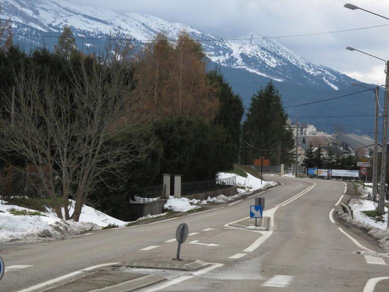 Bild von einer Ortsdurchfahrt im winterlichen Vercors mit Schnee am Straßenrand und auf den nebelverhangenen Bergen