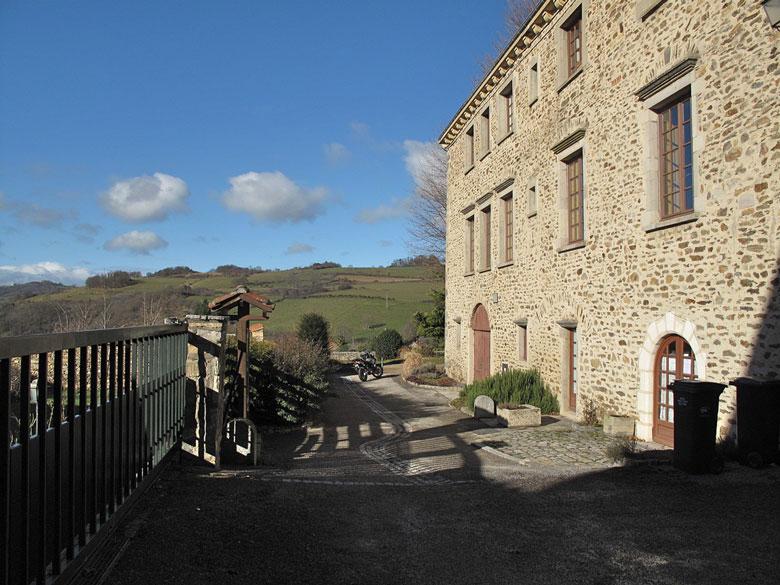 Schloss von Riverie (Département Rhône) bei schönem Wetter mit einem Motorrad im Hintergrund