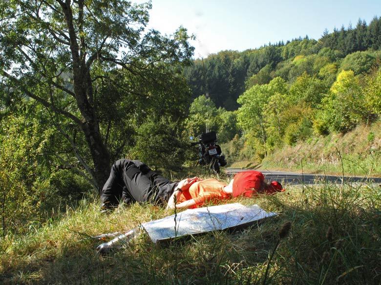 Motorradfahrerin in rotem Shirt im Gras liegend bei einer herbstlichen Ruhepause bei der Holunderernte im Beaujolais