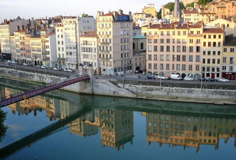 Bind von der Saône in Lyon mit fin de siècle Häuserzeilen am Ufer und einem Fußgängersteg über den Fluß