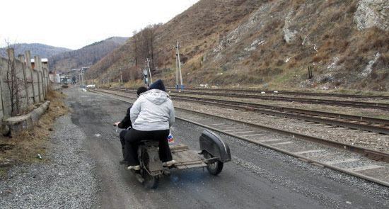 Bild von zwei übergewichtigen Motorradfahrern auf einem umgebauten Ural-Gespann auf einer unbefestigten Straße in Burjätien in der Russischen Föderation