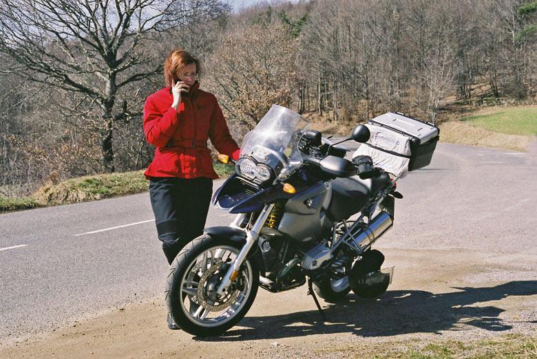 Bild einer Motorradfahrerin in roter Jacke und schwarzer Hose beim Telefonat am Motorrad BMW R 1200 GS