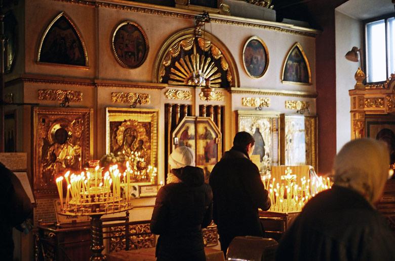 Inneres einer orthodoxen Kirche in Moskau mit Gläubigen und brennenden Kerzen vor einer Ikonostase