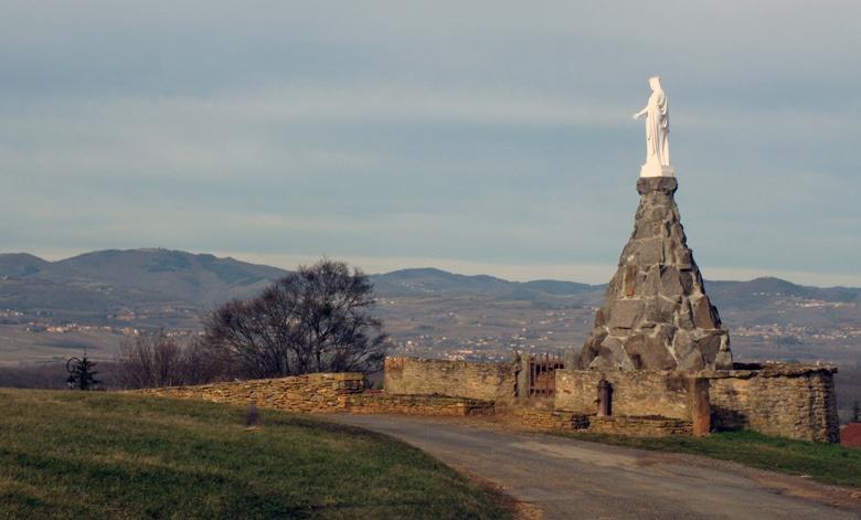 Bild einer Madonnenstatue im Beaujolais mit Bergen im Hintergrund