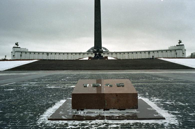 Bild vom Siegesplatz auf dem Poklonnaja Hügel in Moskau im Winter mit der Siegeshalle im Hintergrund und einem Gedenkstein aus rotem Granit mit der Jahreszahl 1945, besucht bei einer vorweihnachtlichen Erkundungstour in Moskau