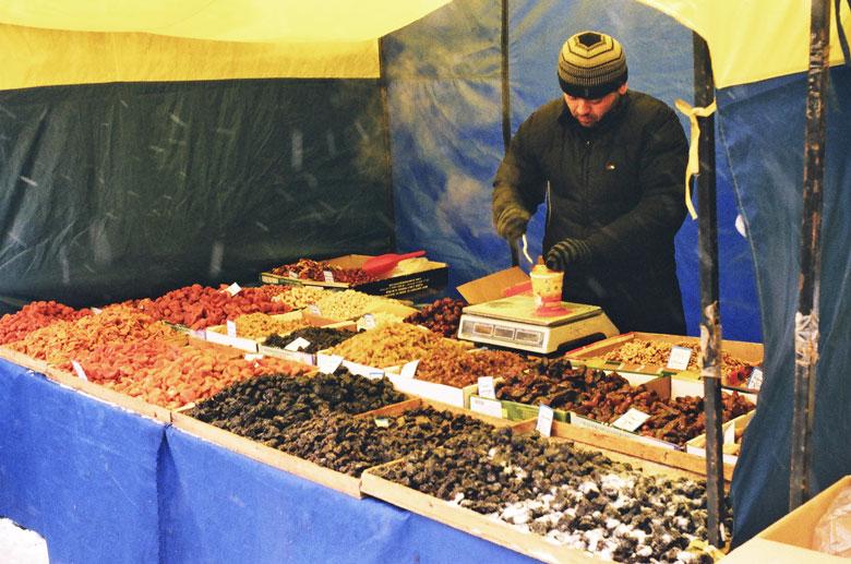 Bild von einem Usbekischer Nussverkäufer auf winterlichem Markt in Moskau mit allerlei Nüssen und Trockenfrüchten aus seiner Heimat im Angebot