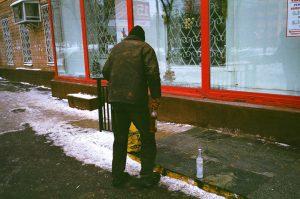 Bild eines Betrunkenen im Winter mit einer Schnapsflasche in der Hand und einer leeren Flasche nebenan auf dem Boden