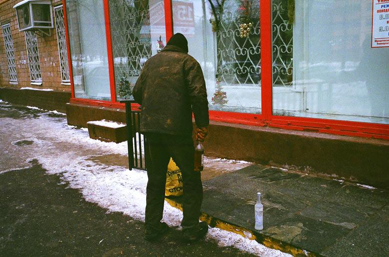 Betrunkener Mann im Moskauer Winter mit einer Schnapsflasche in der Hand vor einem Schaufenster