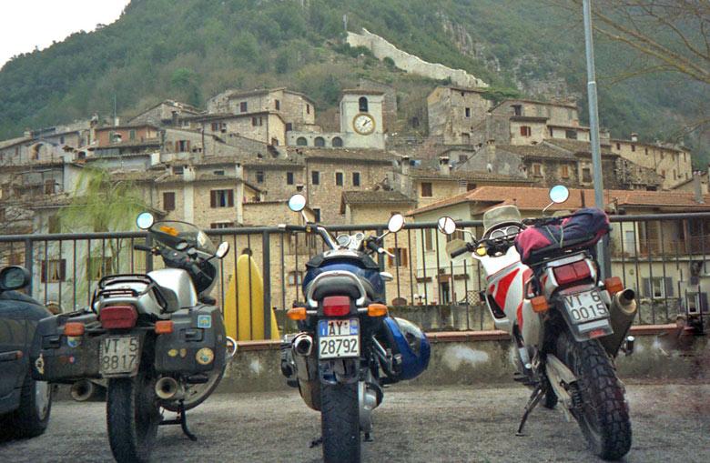 Bild von drei Motorrädern nebeneinander auf einem Parkplatz mit einem Bergdorf im Hintergrund bei einer Motorradtour durch Umbrien